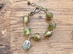 Handmade artisan bracelet featuring a tiny hand carved  ox bone owl amulet, wire work hammered brass and recycled glass beads from Ghana. Earthy-chic and magical!