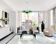 A vintage Stilnovo light fixture hangs in the living room of a diamond dealer's minimalist Manhattan apartment, decorated by Jennifer Post