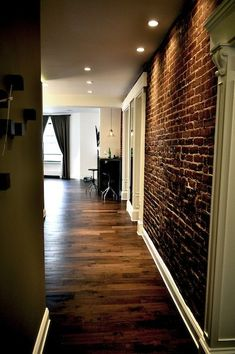 brick wall, white trim, wood floor