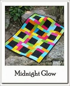 Midnight Glow Quilt Free Tutorial at Freemotion by the River. What a beautiful log cabin style quilt! We love the rainbow contrasting with the black.