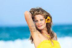 Beautiful woman in yellow dress on the beach Stock Photo