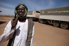 11 February 2014. Shangil Tobaya: A community leader in Nifasha camp for Internally Displaced Persons (IDP), North Darfur, greets in front of the camera at the arrival of World Food Programme (WFP) trucks to the camp to deliver 350 metric tons of food (oil and sorghum) to Nifasha and Shaddad camps for Internally Displaced Persons. Photo by Albert Gonzalez Farran, UNAMID - www.albertgonzalez.net