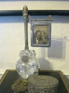 photo display with knife, key, chandelier crystals and glass jar.