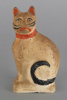 """Small chalkware cat, 19th c., with red and black polychrome decoration, 5"""" h."""