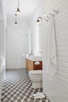 Patterned tile floors, wood vanity, white tile walls
