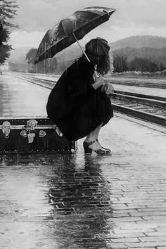 Girl sitting on luggage in the Rain waiting for a Train