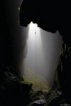 Into A Moss Grown Cave. - Its a Long Climb out.    Caving helmets with lights, climbing gear, caving suits, and all the required equipment...