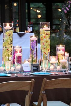 you can get the vases at Dollar Tree for $1 each. 3 bags of the rocks at $1 each, and the floating candles in a 6 pack for $2.99 at Hob Lob. With a super gorgeous orchid as the flower, in the colors of the wedding, you've got yourself a very pretty, and very thrifty centerpiece!