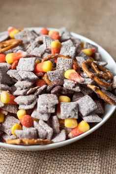 Halloween Muddy Buddy Mix    9 cups Corn or Rice Chex Cereal  1 cup semi-sweet chocolate chips  1/4 cup butter  1/2 cup peanut butter  1 tsp vanilla extract  1 1/2 cups powdered sugar  1 1/2 cups candy corn  1 1/2 cups Reese's Pieces  2 cups pretzels (can be the minis, regular, sticks)
