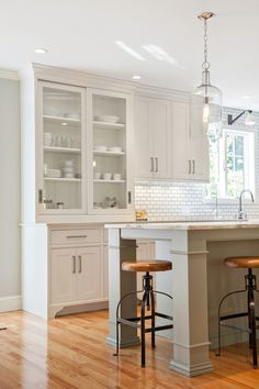 shaker style white kitchen w/grey island, nickel cabinet pulls, built in hutch, light hardwood floor, clear pendants above island, and subway tile backsplash