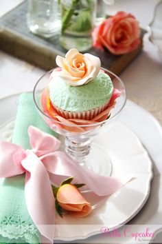 A simple pastel green lace fondant cupcake topped with a peach handmade rose