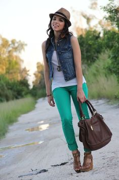 Green skinny jeans, denim vest, white tank top, brown bag, fedora, brown leather wedges, long necklace
