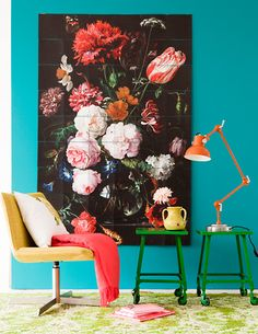 bold turquoise wall, oversize dramatic artwork, brightly colored chairs, lamp and throw.
