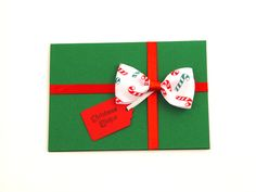 Christmas Gift - A beautiful and versatile folded card made from the highest quality coloured card. Its pure solid colour flows through its surface which features a crisp, original smooth finish. Design features red satin ribbon with a grosgrain beautiful printed ribbon attached to it giving you impression as if you wrapped a present. Final touch a small red gift tag saying 'Merry Christmas'. It comes with green envelope in protective cellobag.