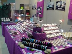 The purple tablecloths and wall hangings pull this jewelry display together very nicely.