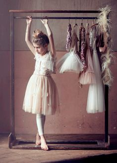 How cute would it be to take a pic like this every year before your little girl's dance recital, with all the previous costumes hanging??