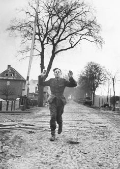 Very young German soldier running with his arms raised in surrender after giving up during the Allied drive towards Berlin. Lemgo, Germany, 1945.