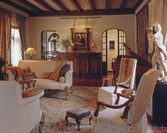 love the slipcovers, arched doors, beams, rug....the mix