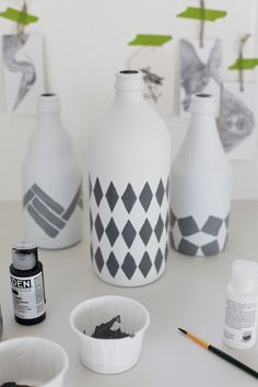 Glass bottles spray painted with a matte white paint then a stencil of acrylic paint color was applied. One can also do numbers, names, etc... via A Creative Mint.