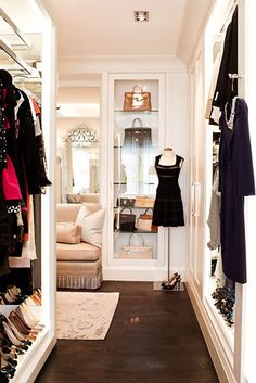gorgeously elegant creamy white dressing room with dark rich hardwoods, dress form, sweet seating, glass front cabinet for fine handbags, sparkling silver accents....