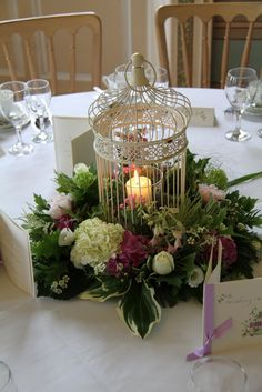 wedding tables, table decorations, wedding table centrepieces, floating candles, bird cage, birdcag, flower designs, vintage birds, table centerpieces