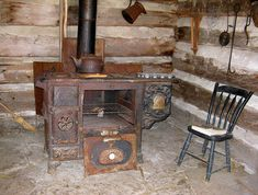 love the ambiance of this old log cabin and wood burning stove!