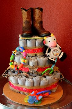Diaper Cake- Western themed with denim diapers and baby cowboy boots! Super easy to make! Just roll diapers with rubber bands, circle them around bottles into three tiers with twine, put a book on top and then add accessories! Takes about 2-3 hours to make.