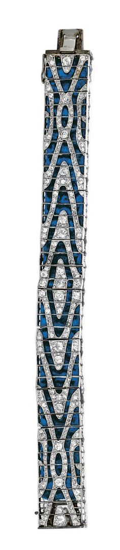 DIAMOND BRACELET, CIRCA 1915.  The articulated open work strap designed as a band of moiré silk, set with circular-, single- and rose-cut diamonds, with deep blue velvet  backing,   one small stone deficient.  length approximately 188mm,