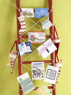 Ladder Christmas Card Display : Make pretty holiday cards part of your decor by displaying them on a painted ladder. Tuck the cards over or between bungee cords screwed in place in an X pattern. Add hooks to the sides to hang stockings or candy-filled cones.