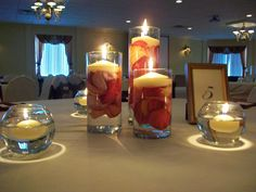 McHale's Events & Catering's 3 Tier Vases with rose petals and floating candles.  A simple, elegant centerpiece.