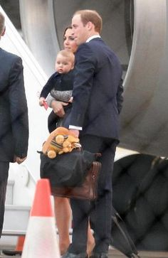 Prince William and Catherine Duchess of Cambridge, aka Kate Middleton, holding Prince George as they transfer planes in Sydney, Australia. She is wearing a wrap dress by Max Mara, her shoes are possibly from Manolo Blahnik, the Suede BB in beige. 4/7/14
