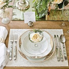 Hand-crafted place mats made with inexpensive wallpaper,   are paired with gold-edged china and simple flatware.