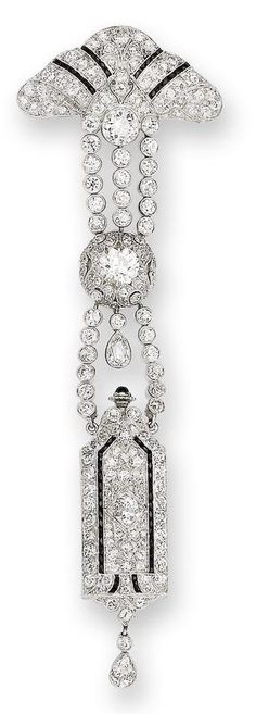 An art deco onyx and diamond lapel watch, circa 1925  Set throughout with calibré-cut onyx and old brilliant-cut diamonds, with millegrain detail, the triangular surmount suspending articulated rows of old brilliant-cut diamonds, terminating in a rectangular fob watch, the dial with Arabic numerals and an engraved bezel, diamonds approximately 6.60 carats total, length 11.2cm.