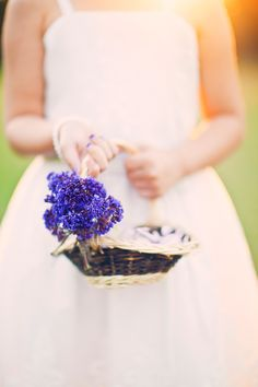 A shallow basket with a bundle of pretty purple flowers on the side!