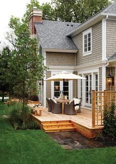 I really like this low profile deck and the rails are cute!  The steps down with the slate is nice.  I also like the planting they did right next to the deck, especially the tree to have some privacy. #outdoor #deck #dining #area #backyard #windows