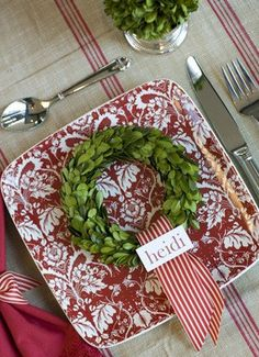 Red, white and green table setting with wreath and ribbon for Christmas place setting