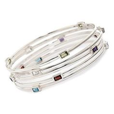 This sterling silver set of five bangle bracelets shows off garnet, peridot, blue topaz, white topaz and amethyst. #stacked >>Click on the gemstone bracelets to see more options. #silver #gemstone #bracelet #braceletset