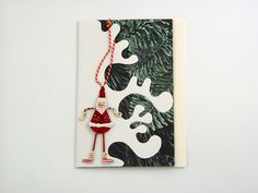 Santa is Coming! - A beautiful and versatile folded card made from the highest quality colored card. Made to look as a Christmas tree covered with snow and decorated with metal Santa, which you too can decorate your own tree with. It comes with white envelope in protective cellobag.