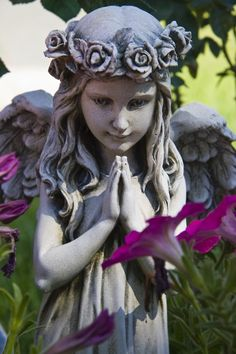Praying Angel in a cemetary -atop of a child's headstone ... with pretty pink flowers in bloom.   ♡
