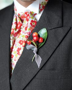 A cherry boutonniere is embellished with striped ribbon