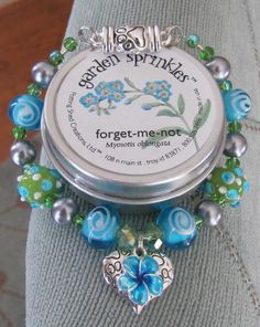 Forget-Me-Not Pet-Lover Memorial Bracelet.  Teal flower forget-me-not flower charm and black heart with paw prints charm on the reverse.  Also features a magnetic paw clasp, and comes with a tin of forget-me-not flower seeds to plant in a pet memorial garden.  Sweet!  $55.00, with 20% of the purchase price of the bracelet donated to the charity/shelter/cause of my customer's choice.