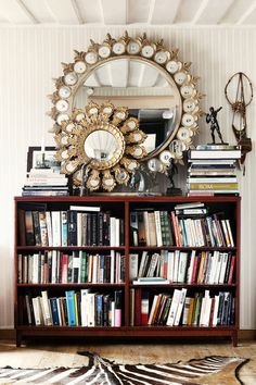 Two round mirrors above a bookcase and a zebra-hide rug.