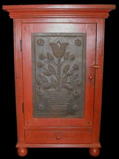 A standing or hanging cupboard with a tulip in a pot motif punched tin door. A fine reproduction!