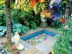 A mosaic pool, kept free of plants and fish so that the beautiful tiles can be clearly seen, serves as the centerpiece for the specimen plants and pots in this patio garden.