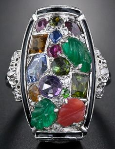 Front view: Tutti-frutti Art Deco dinner ring, circa 1925. An unusual design incorporating carved emeralds, sapphires, rubies, amethysts, citrines, and diamonds within a border of black enamel. Via Diamonds in the Library.