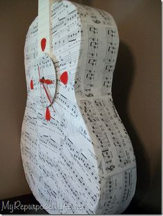 how to: Ugly curbed guitar, decoupaged with sheet music into unique, fun, clock using a cd and guitar picks. Would look great in hubby's music room.