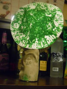 PAPER PLATES PAINTED WITH BOTTOM OF WATER BOTTLES PRINTING WITH GREEN PAINT... TRUNK IS WATER BOTTLE COVERED WITH BROWN MATERAIL SCRAPS... AND THEN TAPES BOTH PLATES TOGETHER AND SIT ON TOP OF WATER BOTTLE... OUR FIRST TUBSHEVAT TREE THIS YEAR...