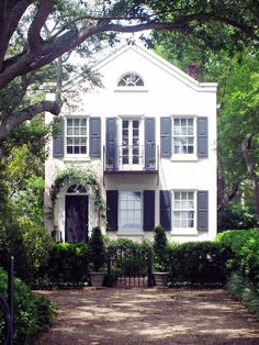 Adorable home.  Love the navy shutters & vined doorway.