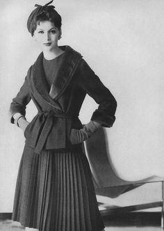 August Vogue 1959    Wearing a dress and jacket in grey flannel by Maurice Rentner.