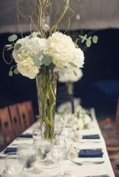 Tall trumpet centerpiece with branches.